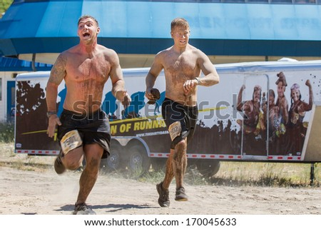 BOISE, IDAHO/USA - AUGUST 10, 2013: Two men run fast to finish the race at the The Dirty Dash - stock photo