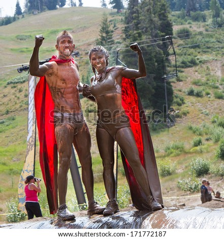 BOISE, IDAHO/USA - AUGUST 11, 2013: Two people dressed as superheros celebrate during the dirty dash - stock photo