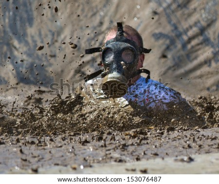 BOISE, IDAHO/USA - AUGUST 10: Unidentified gas masked runner splashes down at the start of the mud pit during the The Dirty Dash in Boise, Idaho on August 10, 2013  - stock photo