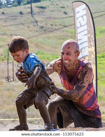 BOISE, IDAHO/USA - AUGUST 11: Unidentified man helps a child up near the finish line of the The Dirty Dash in Boise, Idaho on August 11, 2013  - stock photo