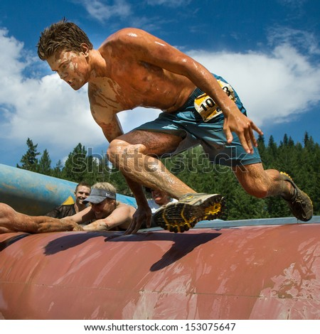 BOISE, IDAHO/USA - AUGUST 11: Unidentified runner jumps over an obstacle at the The Dirty Dash in Boise, Idaho on August 11, 2013  - stock photo