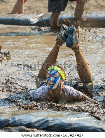 BOISE, IDAHO/USA - AUGUST 10: Unidentified woman fell into the mud pit at the The Dirty Dash in Boise, Idaho on August 10, 2013 - stock photo
