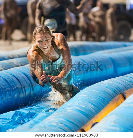 BOISE, IDAHO/USA - AUGUST 25:Unidentified woman jumps to go down the slide. The Dirty dash is a 10k run through obstacles and mud on August 25, 2012 in Boise, Idaho - stock photo