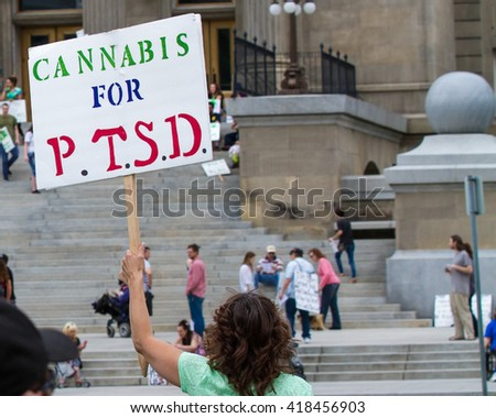 BOISE, IDAHO/USA - MAY 7, 2016: Woman displaying a sign in support for cannabis for PTSD patients for the Global Marijuana March in Boise, Idaho - stock photo