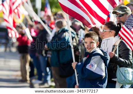 BOISE, IDAHO/USA - NOVEMBER 21, 2015: Child holding up an American Flag at the counter protest to the refugee situation in America - stock photo