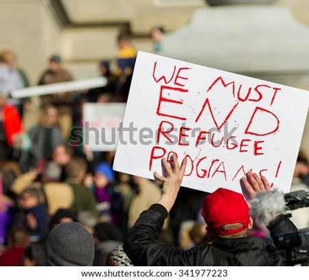 BOISE, IDAHO/USA - NOVEMBER 21, 2015: Protester holding a sign claiming we need to end refugee programs in Boise, Idaho - stock photo