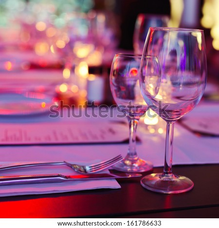 Bokeh background of table in restaurant. Selective focus on reflection in the glass. - stock photo
