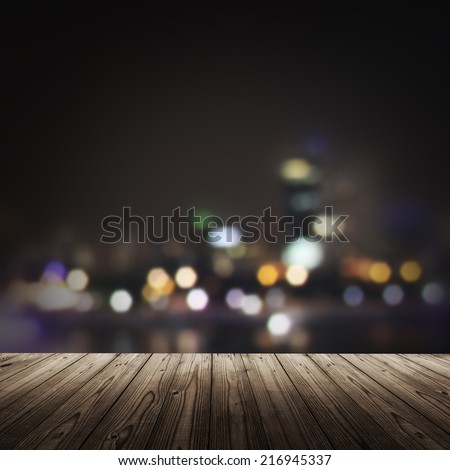 Bokeh background with night city and wooden deck - stock photo
