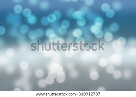 Bokeh blurry winter holidays background in blue and white. Blurry sparkling lights; snowfall. - stock photo