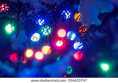 Bokeh Christmas holidays lights defocused background in the frame of fir twigs covered with snow - stock photo
