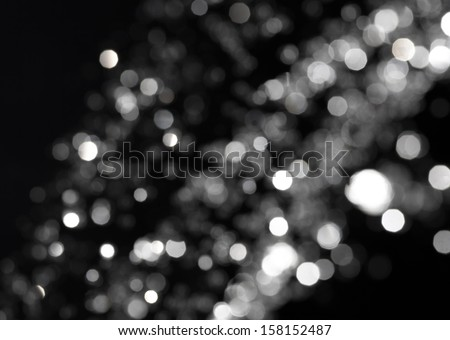 bokeh lights on black background, shot of flying drops of water in the air - stock photo