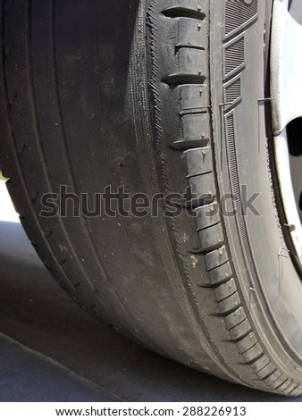 Bold tire with exposed unevenly worn out thread - stock photo