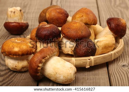 boletus mushrooms in a basket on wooden surface - stock photo