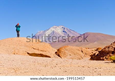 Bolivia, Antiplano - senior tourist and volcano Ollague - stock photo
