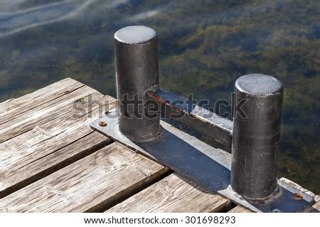 Bollard shabby on the old plank wharf - stock photo