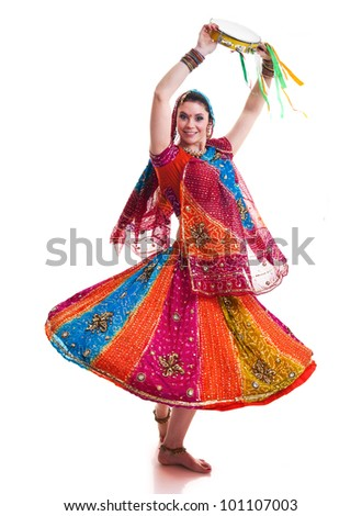 Bollywood dancer in traditional beautiful multicolored dress with veil and tambourine - stock photo