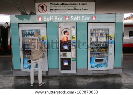 BOLOGNA, ITALY - APRIL 19, 2014: A man buys a snack from an outdoor vending machine in Bologna, Italy, on Saturday, April 19, 2014.  - stock photo