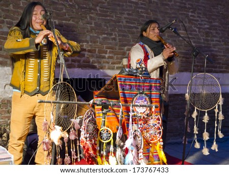 BOLOGNA, ITALY - JANUARY 25, 2014 - Native Indians sell native products while they perform at Piazza Maggiore in Bologna's center. - stock photo
