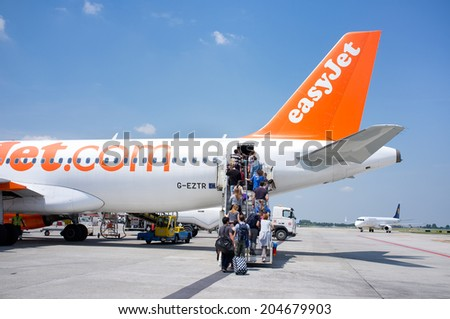 BOLOGNA, ITALY - JUNE 19: People entering an EasyJet plane in Guglielmo Marconi Airport. EasyJet is the low cost airline of the United Kingdom. June 19, 2014 in Bologna, Italy - stock photo
