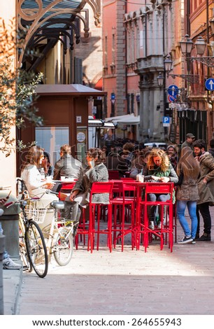 BOLOGNA, ITALY - MARCH 12,2015:Tourists Having Lunch At Outdoor Restaurant Downtown and  people gather around the Piazza Maggiore in Bologna - stock photo
