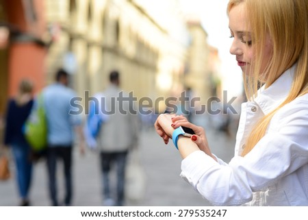 BOLOGNA, ITALY - MAY 17, 2015: One girl looks at the apple watch on her wrist in one of the city center street. - stock photo
