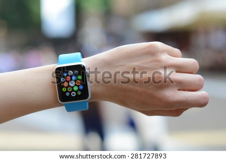 BOLOGNA, ITALY - MAY 17, 2015: One girl wears the apple watch against blurred city background - stock photo