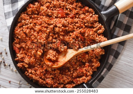 Bolognese sauce in a frying pan close-up on the table. horizontal view from above