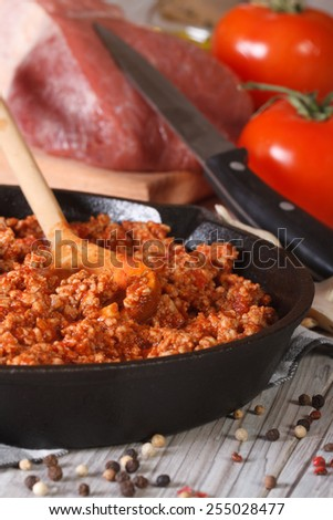 Bolognese sauce in a frying pan close-up on the table. vertical