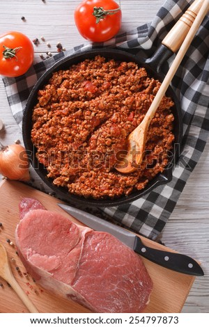 Bolognese sauce in a skillet with the ingredients on the table. vertical top view closeup - stock photo