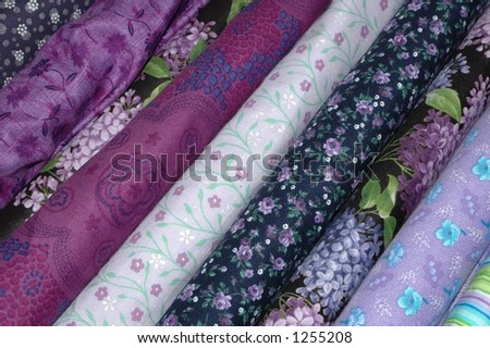 Bolts of quilt fabric in the purple and lavender range. - stock photo