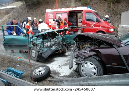 BOLZANO BOZEN, ITALY - JANUARY 20, 2015: Paramedics and Firemen provide first aid to injured motorist after hard collision between two cars on the iced road in winter time on January 20, 2015. - stock photo