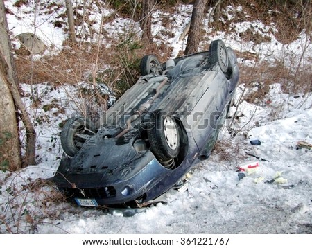 BOLZANO, ITALY - JANUARY 18, 2016: Car flipped over off the road after a collision. Scene of an accident caused by the high speed and the road made treacherous by ice and snow on Bolzano, Italy. - stock photo
