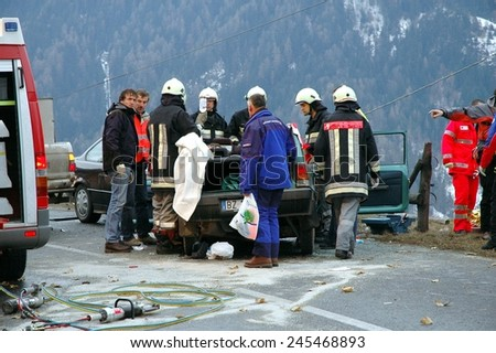 BOLZANO, ITALY - JANUARY 20, 2015: Dramatic crash accident with deadly motorist after frontal collision on iced road. Paramedics and Firemen provide first aid to injured person on January 20, 2015. - stock photo