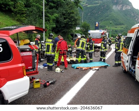 BOLZANO, ITALY - July 18, 2013: Paramedics  Firefighters and police man working after a huge car crash collision. Car accident on the road with injured motorist on the Highway A22 on July 18, 2013. - stock photo