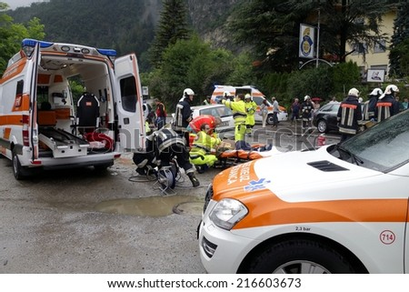 BOLZANO, ITALY - July 28, 2014: Paramedics Firefighters and police man working after a huge car crash collision. Car accident on the road with injured motorist on the road on July 28, 2014. - stock photo