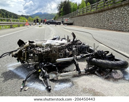 BOLZANO, ITALY - MAY 6, 2013: Fatal motorbike car crash accident after a frontal collision on the road between two cars on the road with intervention of paramedics and firefighters on May 6, 2013 - stock photo