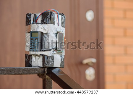 bomb with radio control and digital countdown timer bomb near the door of the house. terrorism and dangerous life concept - stock photo