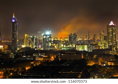 BOMBAY, INDIA - MARCH 4, 2011: Bandra station ablaze with plumage of flames and smoke high into the night sky - stock photo