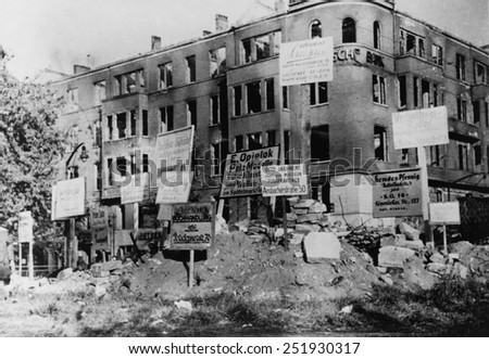 Bombed-out building in Wittenberg Platz, Berlin. Many of the signs posted give directions to merchants' new locations. Photo was taken by Danish photographer Hans Martin Herloff, Ca. March 1945. - stock photo