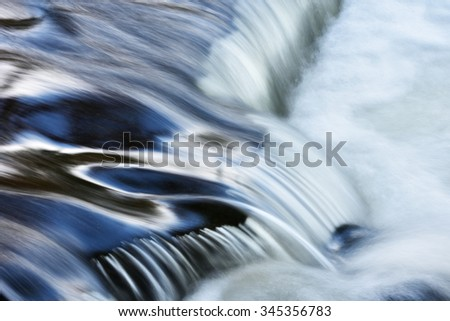Bond Falls cascade captured with motion blur and illuminated by reflected color from blue sky overhead, Michigan's Upper Peninsula, USA - stock photo