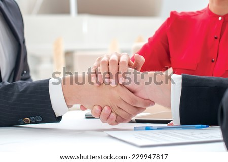 Bond of friendship. Three successful and confident businesspeople shake hands. Businesspeople in formal dress sitting in an office at a desk and smiling at the camera - stock photo