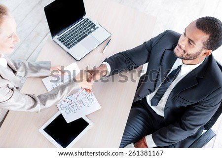 Bond transaction handshake. Two businessman sitting at the table and view the documents. Businessmen shaking hands with each other. - stock photo