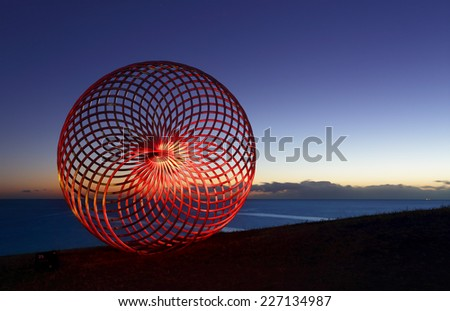 BONDI, AUSTRALIA -  OCTOBER 29, 2014; Sculpture by the Sea Annual Event 2014.  Sculpture titled Sisyphus by George Andric, SA.  Lightpainted with a torch for a red glow.  Materials, stainless steel.   - stock photo