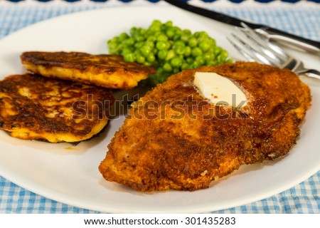 Boneless chicken breast breaded and stuffed with ham and swiss cheese (Cordon Bleu) and served with potato pancakes and English Peas.  Deep fried to golden brown - stock photo