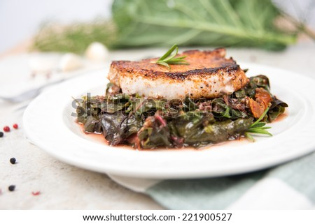 Boneless Grilled Pork Chop Served with Wilted Rainbow Chard and Collard Greens  - stock photo