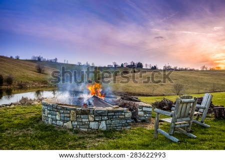 Bonfire in a fire pit at sunset in Central Kentucky countryside - stock photo