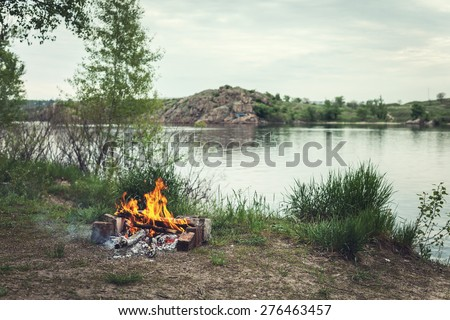 Bonfire in the spring forest. Coals of fire. Twilight in Ukraine - stock photo