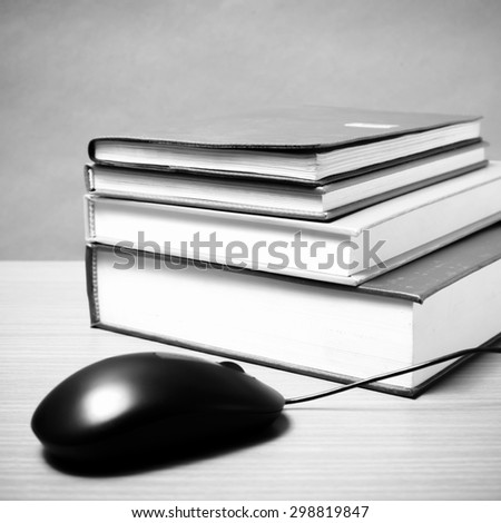 book and computer mouse on wood background black and white color tone style - stock photo