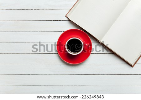 Book and cup of coffee on wooden table. - stock photo