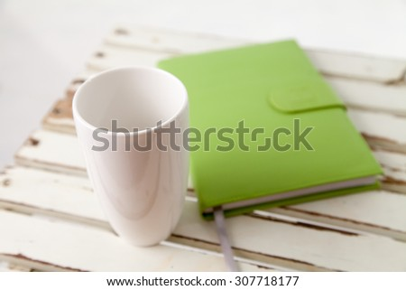 Book and cup on the table in white background - stock photo